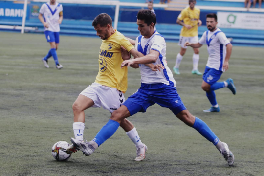 Nando Quesada conduce un balón ante el marcaje de un jugador del Europa   CE Europa